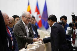 Cambodian Prime Minister Hun Sen, right, shakes hands with the international observer delegations for the July 29 general election, during a welcome meeting in Peace Palace, in Phnom Penh, Cambodia, Saturday, July 28, 2018.