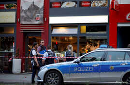 Police stand outside where a 21-year-old Syrian refugee killed a woman with a machete and injured two other people in the city of Reutlingen, Germany, July 24, 2016.