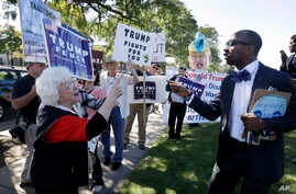 Minister Martez Thompson, right, a supporter of Democratic presidential candidate Hillary Clinton goes up against supporters for Republican presidential candidate Donald Trump outside a campaign stop by Clinton at Wayne State University, Oct. 10, 201