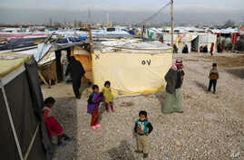 FILE - Syrian refugees stand outside their tents, during the visit of Filippo Grandi, the United Nations High Commissioner for Refugees, UNHCR, to a camp in the town of Saadnayel, in the Bekaa valley, Lebanon, Jan. 22, 2016.