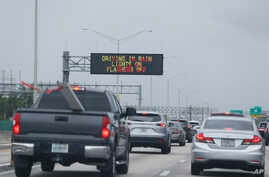 Signs advising drivers to turn on their lights and turn off their flashers while driving in the rain are shown, May 25, 2018, along Interstate 95 near Fort Lauderdale, Fla.