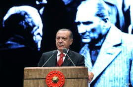 Turkey's President Recep Tayyip Erdogan delivers a speech backdropped by an image of Turkey's founding father Mustafa Kemal Ataturk, right, during a ceremony to mark the 79th anniversary of Ataturk's death, in Ankara, Turkey, Nov. 10, 2017.
