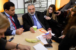 Syrian Information Minister Omran al-Zohbi (2nd L) answers journalists' questions as he takes a break during Syrian peace talks at the United Nations on Jan. 28, 2014 in Geneva.