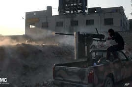 In this citizen journalism image provided by Aleppo Media Center AMC, a Syrian rebel fires a weapon towards Syrian government troops loyal to President Bashar Assad in Aleppo, Syria, Nov. 9, 2013.