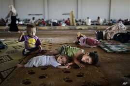 Syrian refugee children try to amuse themselves at a camp near the Turkish border in August of last year.