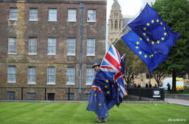 An anti-Brexit protester carries flags opposite the Houses of Parliament in London, Britain, May 10, 2018.