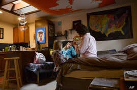 In this Nov. 28, 20017 photo, TC Bell sits with his two daughters Dagny, 8 and Emma, 4 before they get ready for school, at their home in Denver. Bell's daughters are recipients of the Children's Health Insurance Program or CHIP, which is a program t