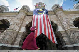 FILE - A Muslim woman walks past a Malaysian flag in front of Sultan Abdul Samad building at Independence Square in Kuala Lumpur, Malaysia.