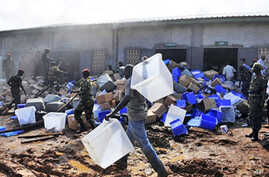 Guinean soldiers remove boxes filled with electoral materials from a warehouse on fire in a military camp in Conakry, 16 Sep 2010