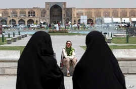 FILE- Iranian women pass a tourist in Isfahan about 400 kms (240 miles) south of Tehran, Iran, May 10, 2006. A U.S. luxury tour company is offering Iran as a new destination.