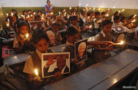 Schoolchildren hold candles and portraits of former South African President Nelson Mandela during a prayer ceremony at a school in the western Indian city of Ahmedabad, Dec. 6, 2013.