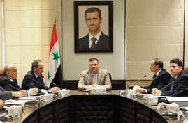 In this undated photo released by the Syrian official news agency SANA on Sunday, Aug. 5, 2012, Syrian Prime Minister Riad Hijab, center, speaks under the portrait of the Syrian President Bashar Assad during a meeting in Damascus, Syria.