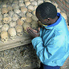 A Rwandan survivor of the 1994 genocide prays over the bones of genocide victims at a mass grave in Nyamata, Rwanda, April 2004. (file photo)