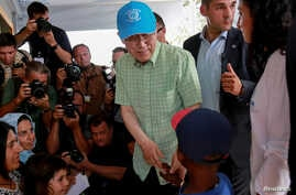 U.N. Secretary-General Ban Ki-moon greets a child during his visit at the municipality-run refugee camp of Kara Tepe on the island of Lesbos, Greece, June 18, 2016.