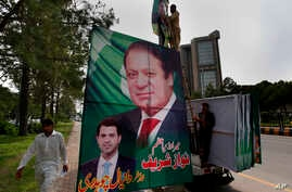 Pakistani workers install a huge billboard of deposed Prime Minister Nawaz Sharif on the planned route of his rally on a highway in Islamabad, Pakistan,  Aug. 8, 2017.