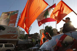 FILE - Lebanese supporters of the Free Patriotic Movement of Christian leader Michel Aoun wave the Lebanese and the party's orange flags as they ride their cars in the Christian stronghold of Metn north of Beirut, Lebanon June 5, 2009.