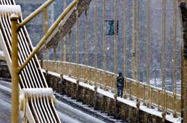 A man walks across the Rachel Carson bridge over the Allegheny River toward downtown Pittsburgh as snow falls during the evening rush hour Jan. 20, 2016.