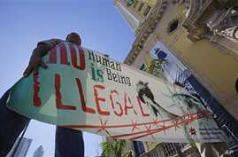 Immigration reform activists hold a sign in front of Freedom Tower in downtown Miami, Jan. 28, 2013.