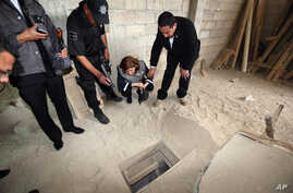 """In this photo provided by Mexico's attorney general, authorities inspect the exit of the tunnel they claim was used by drug lord Joaquin """"El Chapo"""" Guzman to break out of the Altiplano maximum security prison in Almoloya, west of Mexico City, July 12..."""