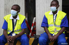 Airport workers in Abidjan protect themselves from the spread of the Ebola virus disease in Abidjan, August 12.