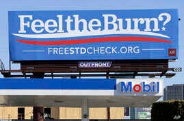 """FILE - This April 1, 2016 file photos shows a billboard above a gas station that reads """"Feel The Burn,"""" a play on then-presidential candidate Bernie Sanders' campaign slogan, """"Feel The Bern."""" It's actually promoting testing for sexually transmitted d"""