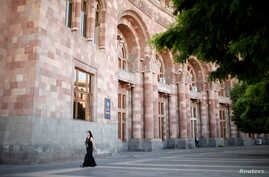 A woman walks in front of the government headquarters at the Republic Square in Yerevan, Armenia, May 3, 2018.
