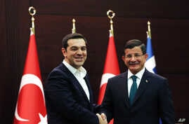 Greece's Prime Minister Alexis Tsipras (l) and his Turkish counterpart Ahmet Davutoglu shake hands after a joint news conference at Cankaya Palace in Ankara, Turkey, Nov. 18, 2015.