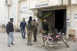 Rebel fighters stand outside Idlib museum in Idlib, Syria, after Islamist rebel fighters took control of the area, April 1, 2015.