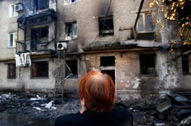 A woman cries in front of her damaged apartment building after shelling in the town of Donetsk, eastern Ukraine, Sept. 17, 2014.