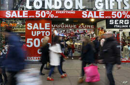 FILE - Shoppers pass a sale sign on Oxford Street in London, Dec. 22, 2014.