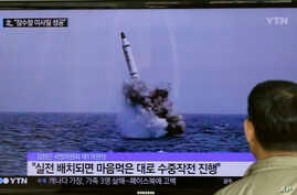 A South Korean man watches a TV news program showing an image published in North Korea's Rodong Sinmun newspaper of North Korea's ballistic missile believed to have been launched from underwater, at Seoul Railway station in Seoul, South Korea,  May 9...