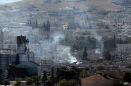 Smoke from a fire rises following a strike in Kobani, Syria, during fighting between Syrian Kurds and the militants of Islamic State group, as seen from a hilltop on the outskirts of Suruc, at the Turkey-Syria border, Tuesday, Oct. 21, 2014. The buil...