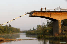 Ukrainian servicemen stand on a bridge ruined during battles between the Ukrainian army and pro-Russian separatists on the outskirts of Slaviansk, in the Donetsk region August 8, 2014. REUTERS/Valentyn Ogirenko (UKRAINE - Tags: MILITARY CONFLICT CIVI