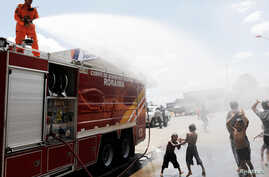A Brazilian firefighter sprays water to cool Venezuelans outside a gym which has become a shelter for Venezuelans in Boa Vista, Brazil Nov. 18, 2017.