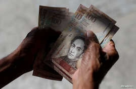 A man counts Venezuelan bolivar notes in downtown Caracas, Venezuela, Jan. 9, 2018.