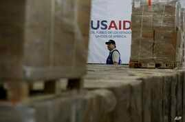 A man walks past boxes of USAID humanitarian aid at a warehouse at the Tienditas International Bridge on the outskirts of Cucuta, Colombia, Feb. 21, 2019, on the border with Venezuela.