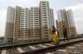 A woman carrying a child walks ahead of her husband on a railway track in front of residential buildings under construction on the outskirts of Kolkata, India, April 26, 2012.