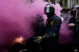 Catalan Mossos d'Esquadra regional police officers stand amid smoke from a smoke bomb during clashes with pro-independence supporters trying to reach the Spanish government office in Barcelona, Spain, Sunday, March 25, 2018.