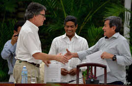 FILE - The head of the Colombian government delegation for the peace talks with the ELN guerrillas Gustavo Bell, left, and The chief negotiator of Colombia's last rebel group, the National Liberation Army (ELN), Pablo Beltran, shake hands during the