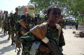 A youth leads a group of hard-line Islamist Al Shabab fighters as they conduct military exercises in northern Mogadishu's Suqaholaha neighborhood, Somalia, Jan. 1, 2010.