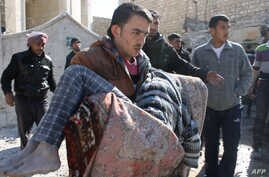 A man carries a body following a reported Syrian government forces air strike in the northern city of Aleppo on Feb. 4, 2014.