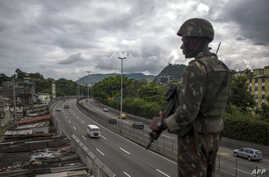 """A Brazilian army soldier stands guard over the """"Linha Amarela"""" (yellow line) road during a joint operation at """"Cidade de Deus"""" (City of God) favela in Rio de Janeiro, Feb. 07, 2018."""