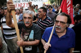 Greek protesters shout slogans as they march during a rally against the visit of the German Finance Minister Wolfgang Schaeuble in Athens, July 18, 2013.