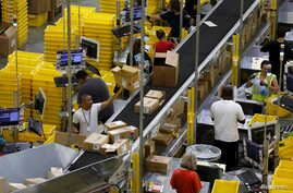 FILE - Workers sort arriving products at an Amazon Fulfilment Center in Tracy, California, August 3, 2015.