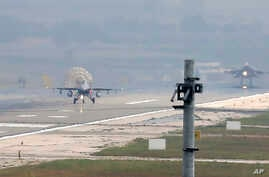 Turkish Air Force fighter planes land at Incirlik Air Base, on the outskirts of the city of Adana, southern Turkey, Thursday, July 30, 2015.