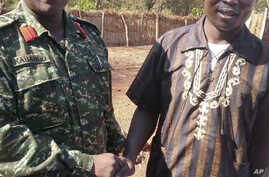 FILE - In this photo released by the Uganda People's Defense Force (UPDF), Ugandan Contingent Commander to the African Union Regional Task Force Col Michael Kabango, left, talks with a man in  UPDF custody said by the UPDF to be the wanted Lord's Res