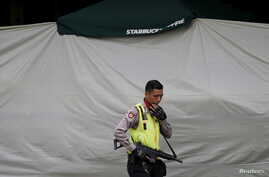 An Indonesian policeman holds a rifle as he guards near Starbucks cafe in Jakarta, Jan. 15, 2016.