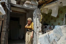A local woman reacts next to her destroyed home after shelling in pro-Russian rebels controlled Staromykhaylivka village near of Donetsk, Ukraine, 24 May 2016.