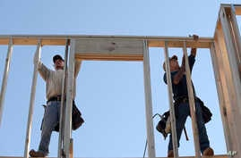 In this Feb. 13, 2015 photo, construction workers David Rager, right, and Shawn White frame the upper floor of a home being built in Orlando, Fla.