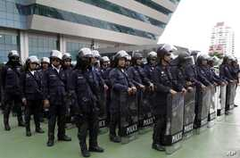 Thai riot policemen stand guard outside the Constitution Court during a ruling Friday, July 13, 2012 in Bangkok, Thailand.